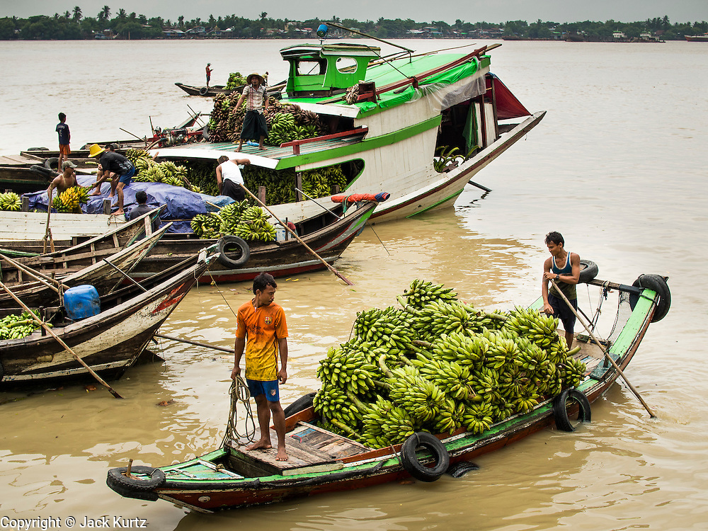 "10 JUNE 2014 - YANGON, MYANMAR:   A small banana boat comes into shore at that banana jetty. The ""banana jetty"" is on the Yangon River north of central Yangon on Strand Road. Bananas, coconuts and other fruit are brought in here from upcountry, sold and reshipped to other parts of Myanmar (Burma). All of the labor here is done by hand. Porters carry the produce to the jetty and porters load the boats before they steam upriver.   PHOTO BY JACK KURTZ"