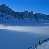 A mountaineers hikes above the remote, cloud-filled Stewart Valley on Canada's Baffin Island - a landscaped akin to California's Yosemite.