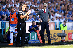 Arsenal manager Arsene Wenger (right) and Huddersfield Town manager David Wagner and Abdelhamid Sabiri watch the action from the touchline