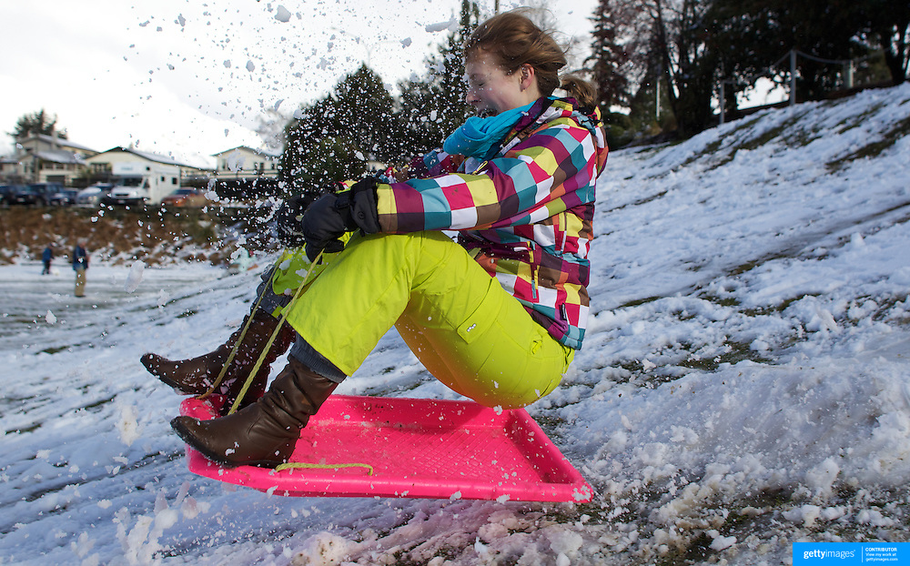 Victoria Lyon, 23, from Dunedin has fun in the snow on a sledge in the Queenstown Recreation Grounds after fresh winter snow falls. Queenstown, Central Otago, South Island, New Zealand. 10th July 2011. Photo Tim Clayton