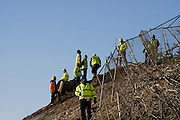 Security men on the slope of Rath Lugh, where the M3 Motorway cuts through it. Rath Lugh is an ancient bronze age promontory fort currently tagged for considerable damage destruction by the construction of the M3 motorway between Dublin and Navan. Protestors are camped in the woods, in oposition to the construction work. ..