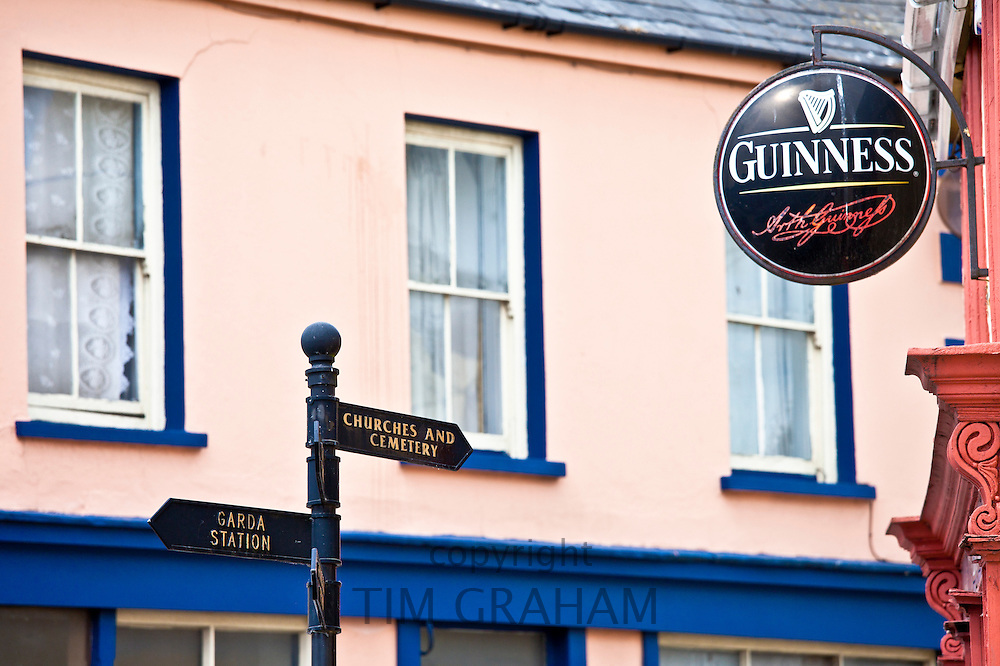 Signpost to Garda, Churches and Cemetery next to Guinness advertisement at bar in Timoleague, West Cork, Ireland