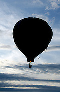 Hot air balloon silhouetted against afternoon clouds, Crown of Maine Balloon Fair, Presque Isle, Maine.