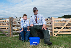 © Licensed to London News Pictures. <br /> 13/08/2014. <br /> <br /> Danby, North Yorkshire, United Kingdom<br /> <br /> Jack Harland, 5 and his father Nick sit outside the pen containing their Blue Faced Leicester sheep during the Danby Agricultural Show in North Yorkshire. <br /> <br /> This year is the 154th show which was founded in 1848. It is the oldest agricultural show in the area and offers sheep dog trials, judging of a variety of different animals such as cattle, sheep, ferrets, horses and rabbits along with different classes of horticulture and dairy. <br /> <br /> Photo credit : Ian Forsyth/LNP