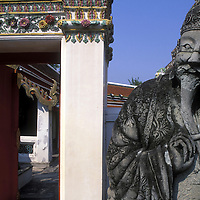 Asia, Thailand, Bangkok, Detail of finely carved statue of monk standing by gate within Wat Pho Buddhist Temple