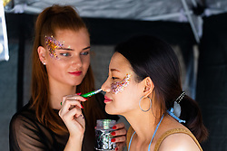 A woman paints glitter onto a reveller as day one, Children's Day, of the Notting Hill Carnival gets underway in London. London, August 25 2019.