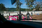 Street vendors who sell plastic flowers for parties such as weddings approach the car.