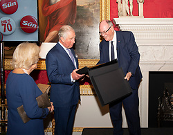 The Prince of Wales and the Duchess of Cornwall are presented with a book from photographer Arthur Edwards during a tea party held at Spencer House in London to celebrate 70 inspirational people marking their 70th birthday this year.