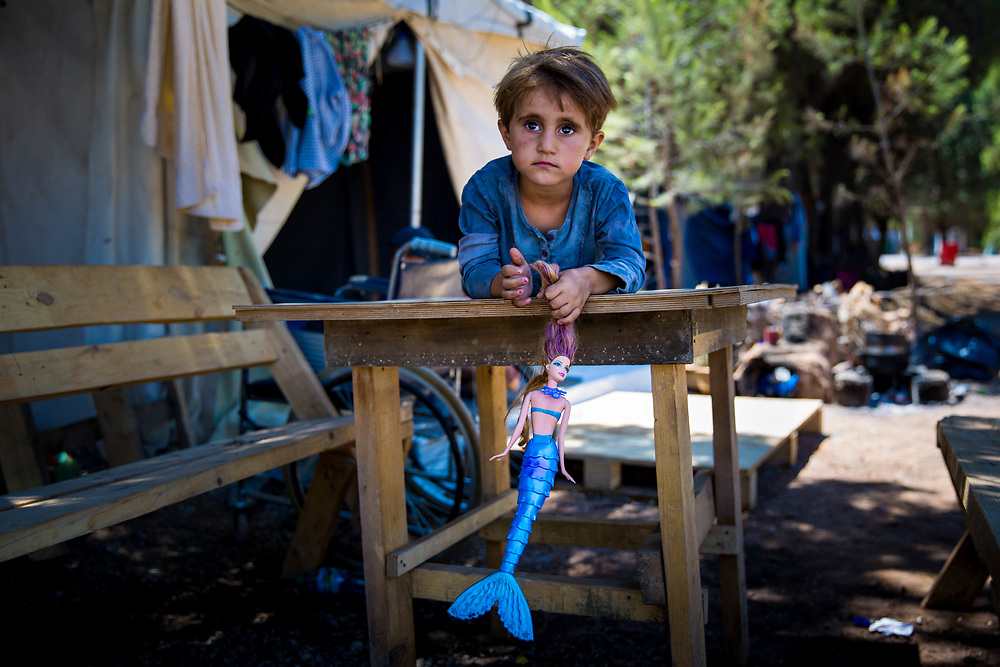 """Najah, 4, a Kurdish Syrian refugee from Aleppo, plays on a table her Grandpa Jameel made, which sits outside of her family's tent in Ritsona refugee camp, an hour north of Athens, Greece. <br /> <br /> extended family have been stranded in Greece since they arrived in March 2016, after the Balkan borders were closed to all refugees. Referring to their extended family, Grandpa Jameel said, """"We are happy to go anywhere, as long as we can stay together."""""""