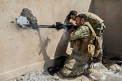 April 19, 2017 - Mosul, Nineveh Province, Iraq - An Iraqi soldier fires on ISIS positions. The recapture of al-Thawra neighborhood is part of a push toward the western edge of Mosul's densely populated old city center. (Credit Image: © Gabriel Romero via ZUMA Wire)