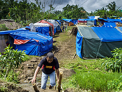 January 29, 2018 - Santo Domingo, Albay, Philippines - A man leaves an impromptu camp in Santo Domingo for people evacuated from their homes because of the Mayon volcano. Many of the shelters in Santo Domingo are filled beyond capacity and people are sleeping tents and huts along the roads.  Mayon volcano's eruptions continued Monday. At last count, more 80,000 people have been evacuated from their homes of the slopes of the volcano and are crowded into shelters in communities outside of the danger zone. (Credit Image: © Jack Kurtz via ZUMA Wire)
