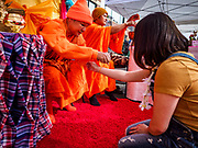 """29 APRIL 2017 - MINNEAPOLIS, MINNESOTA: Thai Buddhist monks bless people during the Songkran Uptown celebration. Several thousand people attended Songkran Uptown on Hennepin Ave in Minneapolis for the city's first celebration of Songkran, the traditional Thai New Year. Events included a Thai parade, a performance of the Ramakien (the Thai version of the Indian Ramayana), a """"Ladyboy"""" (drag queen) show, and Thai street food.     PHOTO BY JACK KURTZ"""