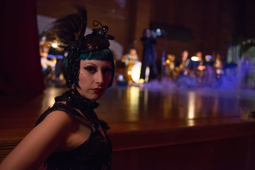 A woman in costume stands by the stage as the Ghost Train Orchestra plays.