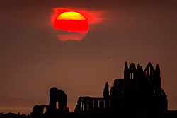 © Licensed to London News Pictures. 24/06/2020. Whitby, UK. The sun glows red as it begins to set behind the gothic ruins of Whitby Abbey on the Yorkshire coast last night. Photo credit: Andrew McCaren/LNP