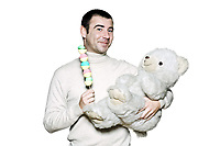 Portrait of a childish mature man with a toy and teddy bear in studio on white isolated background