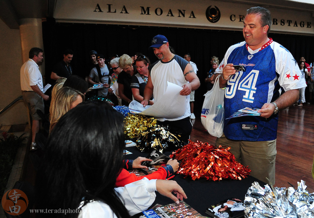 January 28, 2011; Honolulu, HI, USA; A Pro Bowl fan smiles while receiving autographs from cheerleaders during a 2011 Pro Bowl cheerleader appearance at the Ala Moana Center. Mandatory Credit: Kyle Terada-Terada Photo