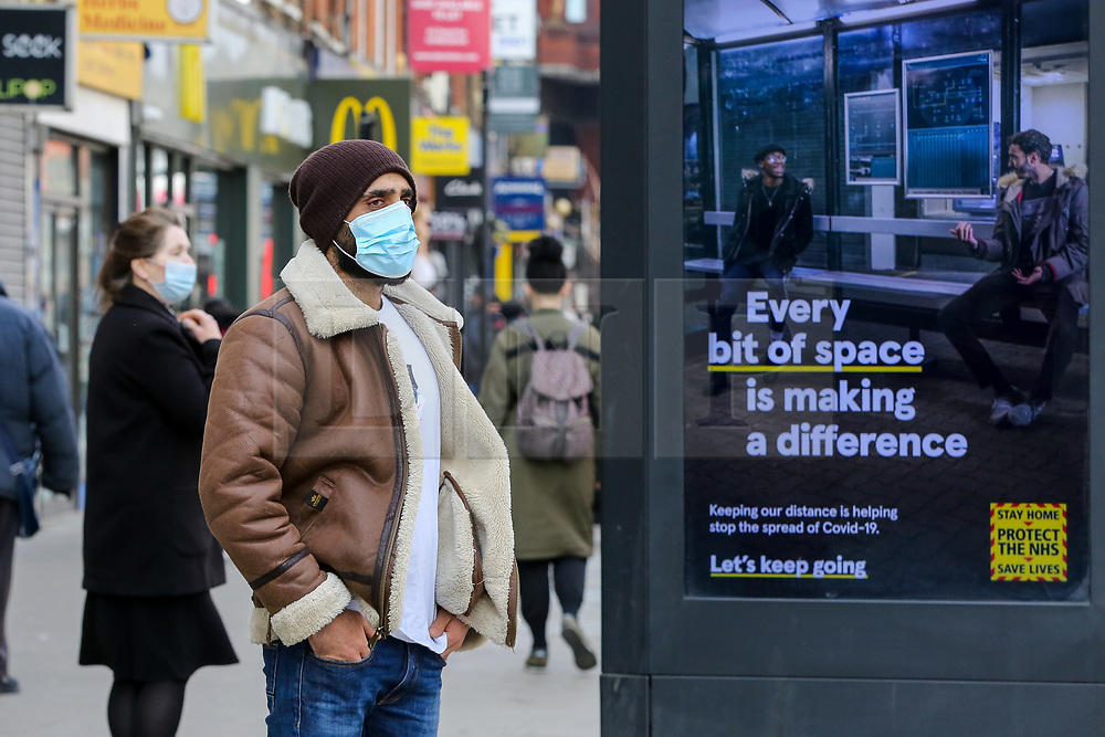 © Licensed to London News Pictures. 23/03/2021. London, UK. A woman wearing a protective face covering stands next to the government's 'Every bit of space is making a difference' poster in north London on the anniversary of the first Covid-19 lockdown in the UK. The next key date for restrictions easing is Monday 29 March 2021, when the 'Stay at Home' guidance will be dropped. Photo credit: Dinendra Haria/LNP