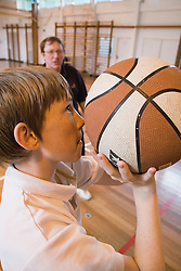 Teacher watches as secondary school student aims for the goal in a game of basketball,