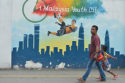 March 23, 2018 - Tanjung Malim, Malaysia - A man with his son passes by a mural '1st Malaysia Youth CIty' near the finish line of the sixth stage, the 108.5km from Tapah to Tanjung Malim, of the 2018 Le Tour de Langkawi. .On Friday, March 23, 2018, in Tanjung Malim, Malaysia. (Credit Image: © Artur Widak/NurPhoto via ZUMA Press)