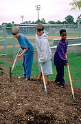 Kids age 12 working at little league baseball field.  St Paul  Minnesota USA