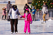 03 JANUARY 2021 - DES MOINES, IOWA: People ice skate at Brenton Skating Plaza in downtown Des Moines. The ice skating rink usually opens in late November and stays open through late February or March, depending on weather. Covid restrictions limited capacity to less than half, skaters were encouraged to social distance, and skaters were required to wear proper face masks. This year the rink was forced to close January 3, after only six weeks, because it wasn't possible to comply with COVID-19 restrictions and still be profitable. Restrictions caused by the Coronavirus pandemic have limited many public events this winter in Iowa.   PHOTO BY JACK KURTZ