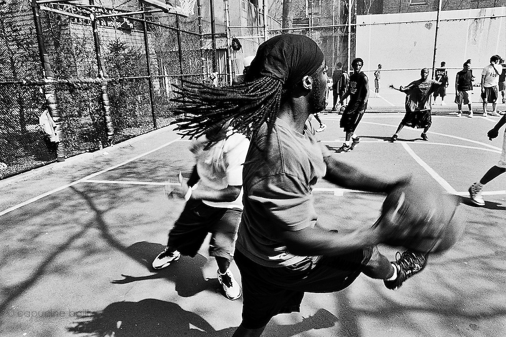 """April 19th 2008. New York, New York. United States..Located in the heart of Greenwich Village, the West 4th Street basketball Court, known as """"The Cage"""", offers no seating but attracts the best players and a lot of spectators as soon as spring is around the corner..Half the size of a regular basketball court, it creates a fast, high level of play. The more people watch, the more intense the games get. « The Cage » is a free show. Amazing actions, insults and fights sometimes, create tensions among and inside the teams. The strongest impose their rules. Charisma is present..""""The Cage"""" is a microcosm. It's a meeting point for the African American street culture of New York. Often originally from Jamaica or other islands of the Caribbean, they hang out, talk, joke, laugh, comment the game, smoke… Whether they play or not, they're here, inside """"The Cage"""". Everybody knows everybody, they all greet each other, they shake hands and hug: """"Yo, whasup man?"""""""