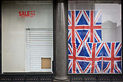 British Union jack flags-themed tourist window, now closed with displays removed after recent sale. The business was on Oxford Street in London's West End and specialised in tourism trinkets before closing, its window display removed except for the flags and lettering telling us the last Sale gave up to 75% discounts on selected items. The scene left by the owners is that of a sad end to another business forced to close by economic hardship. Even the space for the 6th flag seems tragic.