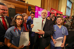 © Licensed to London News Pictures. 27/11/2019. London, UK. Jeremy Corbyn holds up redacted documents that are secret talks between the Government and the US on the NHS with NHS staff. Jeremy Corbyn and Barry Gardiner arrived earlier at Church House, London to announce a major statement on the NHS. Photo credit: Alex Lentati/LNP