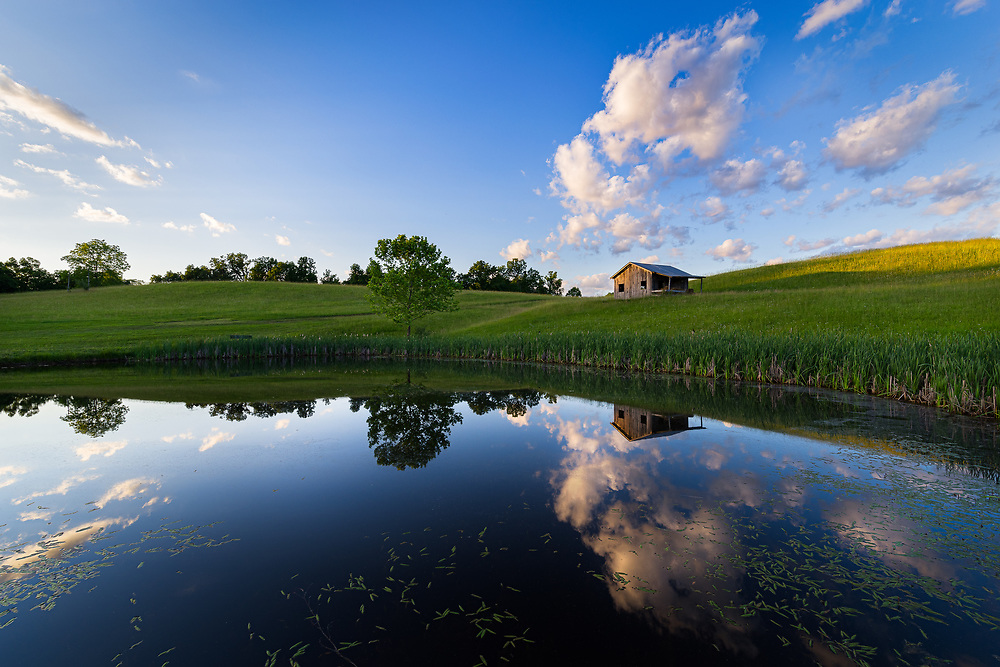 Soft evening clouds converge over the small reflecting pond of Calhoun County Park in West Virginia
