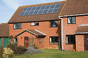 Photovoltaic solar panels on roof of modern suburban house, Martlesham, Suffolk, England