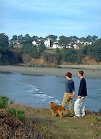 Couple with dog enjoying the view of Big River Beach and Mendocino, California
