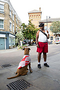 A man with a dog wearing a St Georges Cross Flag on the 23rd June 2018 at Herne Hill in the United Kingdom.