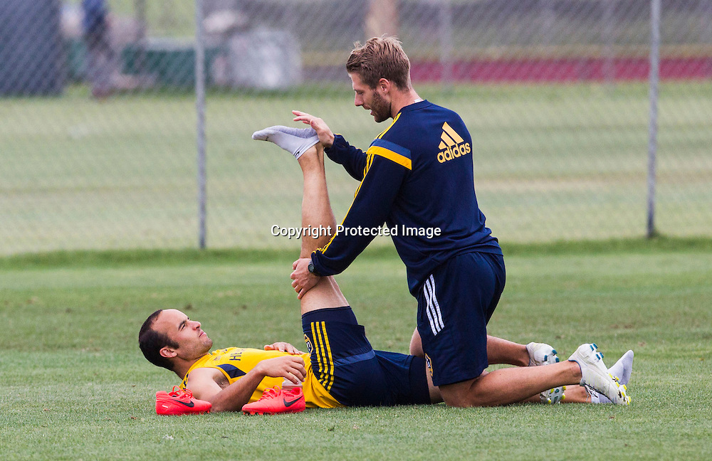 LA Galaxy forward Landon Donovan is assisted in stretching by trainer Kurt Andrews during a training session at StubHub Center in Carson, Calif., Saturday, May 24, 2014. Donovan, the most accomplished American player in the history of men's soccer, won't be going to his fourth World Cup. The 32-year-old attacker, who set the national team record for goals and assists while winning five titles in Major League Soccer, was among seven players cut Thursday when coach Jurgen Klinsmann got down to the 23-man limit well before the June 2 deadline. (AP Photo/Ringo H.W. Chiu)