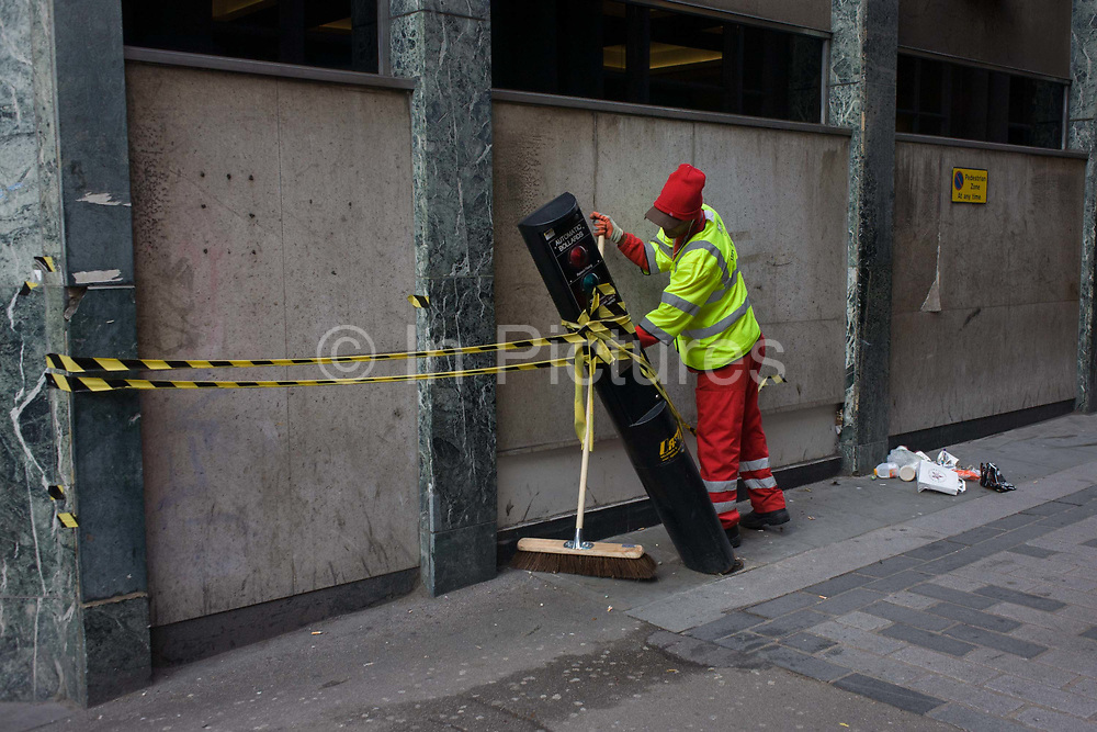 A street sweeper with contractor Amey brushes round a leaning automatic traffic control bollard in St . Swithins Lane, City of London. The workman wears a high-vis jacket and trousers with a bright red hat and he reaches awkwardly behind the damaged pole that leans at an odd angle, seemingly hit by a vehicle. Behind him is swept litter that he will deposit into his bin trolley. It is an odd scene of irregularity in otherwise regimented urban streets of the capital's financial centre aka The Square Mile, founded by the Romans in the 1st century.