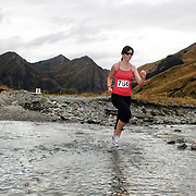 Runner Zara Kingsbury crosses  Moke Creek on the Ben Lomond High Country Station during the Pure South Shotover Moonlight Mountain Marathon and trail runs. Moke Lake, Queenstown, New Zealand. 4th February 2012. Photo Tim Clayton