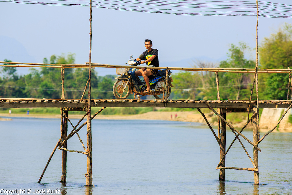 09 MARCH 2013 - ALONG HIGHWAY 13, LAOS:  A man rides his motorcycle across a season bridge over the Nam Song River in Vang Vieng. The bridge connects communities on the west side of the river to Highway 13. The paving of Highway 13 from Vientiane to near the Chinese border has changed the way of life in rural Laos. Villagers near Luang Prabang used to have to take unreliable boats that took three hours round trip to get from the homes to the tourist center of Luang Prabang, now they take a 40 minute round trip bus ride. North of Luang Prabang, paving the highway has been an opportunity for China to use Laos as a transshipping point. Chinese merchandise now goes through Laos to Thailand where it's put on Thai trains and taken to the deep water port east of Bangkok. The Chinese have also expanded their economic empire into Laos. Chinese hotels and businesses are common in northern Laos and in some cities, like Oudomxay, are now up to 40% percent. As the roads are paved, more people move away from their traditional homes in the mountains of Laos and crowd the side of the road living off tourists' and truck drivers.    PHOTO BY JACK KURTZ