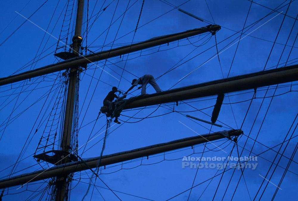 USA - Newport, RI - Crew works at installing anti chaffing gear on a yardarm of the tall ship Kruzenstern.
