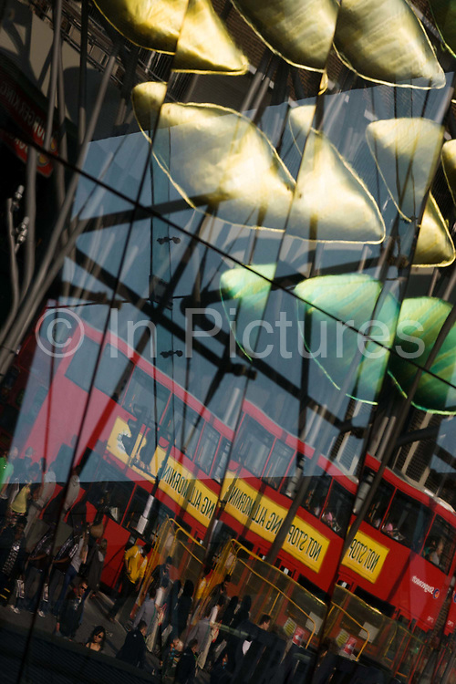 Reflected in the station glass, a red London double-decker bus and commuters at Stratford station. Architecture of Stratford station in east London, the rail transport hub and main arrival point for the 2012 Olympics. The low-level station was substantially rebuilt in the late 1990s as part of the Jubilee Line Extension works, with a large new steel and glass building designed by Wilkinson Eyre that encloses much of the low-level station, and a new ticket hall. Stratford station is a large multilevel railway station in Stratford, east London. The station is served by the National Rail services National Express East Anglia, London Overground and c2c, by London Underground's Central and Jubilee lines, and by the Docklands Light Railway (DLR). Stratford is in London Travelcard Zone 3, and Network Rail owns the station.