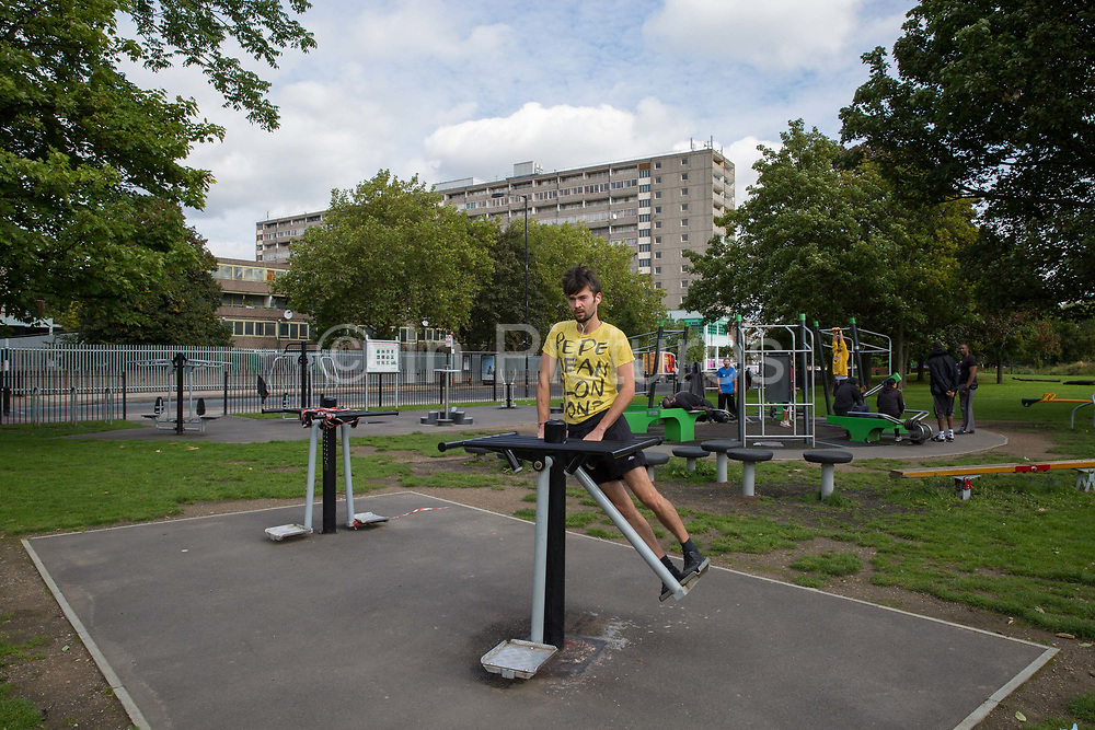 A man working out on outdoor gym equipment in Burgess Park on 17th September 2015 in South London, United Kingdom. On the horizon is the Aylesbury Estate, a large housing estate located in Walworth, South East London. It contains 2,704 dwellings and was built between 1963 and 1977. The whole estate is currently undergoing a major redevelopment with most of the dwellings are derelict.