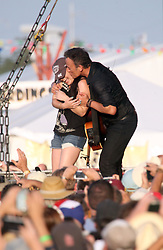 29 April 2012. New Orleans, Louisiana,  USA. <br /> New Orleans Jazz and Heritage Festival. <br /> Bruce Springsteen picks an unsuspecting woman from the audience and pulls her up on stage for a dance and a kiss.<br /> Photo; Charlie Varley/varleypix.com