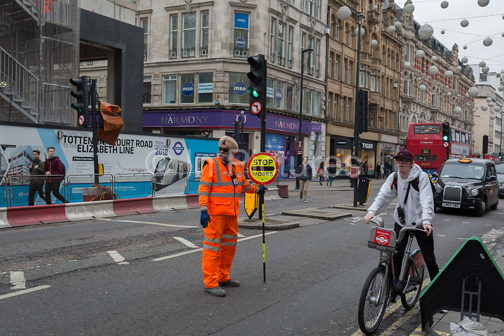 A Sikh wears his traditional turban as he stops traffic on Oxford Street, on 19th October 2017, in London, England.