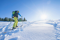 Rear view of skier walking on snow against sky