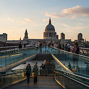 People walking along Millendium Bridge across the Thames in the late afternoon light. In the distance is the dome of St Paul's Cathedral, one of the most distinctive of London's landmarks. There has been a church on this site since 604 AD. The current building, with it's massive dome, was designed by Christopher Wren and dates back to the late 17th century.