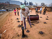 03 MARCH 2017 - BAGMATI, NEPAL: A worker pours coal dust into a kiln at a brick factory in Bagmati, near Bhaktapur. Most of the kilns burn coal imported from India. There are almost 50 brick factories in the valley near Bagmati. The brick makers are very busy making bricks for the reconstruction of Kathmandu, Bhaktapur and other cities in the Kathmandu valley that were badly damaged by the 2015 Nepal Earthquake. The brick factories have been in the Bagmati area for centuries because the local clay is a popular raw material for the bricks. Most of the workers in the brick factories are migrant workers from southern Nepal.       PHOTO BY JACK KURTZ