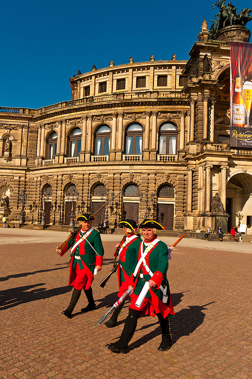 Men dressed as soldiers in historical costume walked past the Semper Opera House, Theaterplatz, Dresden, Saxony, Germany