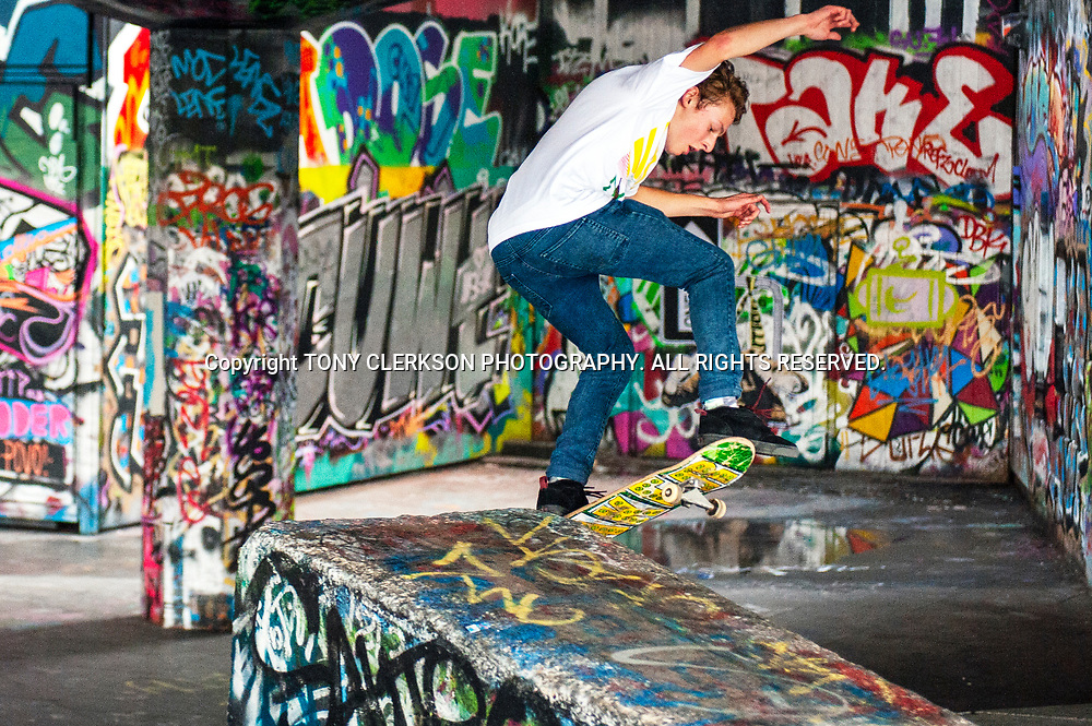 A skateboarder executes some tricks at the South Bank in London