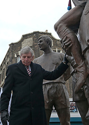 © Licensed to London News Pictures. 24_02_2013..Bobby Moore Wreath laying..Martin Peters touches the knee of the Statue of Bobby Moore..During the memeorial service to mark 20 years since the England and West Ham Utd Captain died of cancer at the age of 51.. Photo credit : Andrew Baker/LNP