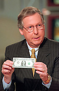 U.S Senator Mitch McConnell holds a dollar bill during discussions on the Republican tax cuts on NBC's Meet the Press August 1, 1999 in Washington, DC.