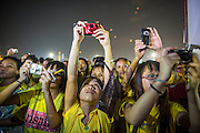 05 DECEMBER 2012 - BANGKOK, THAILAND: Thais strain to photograph the dais during the public ceremony to celebrate the birthday of Bhumibol Adulyadej, the King of Thailand, on Sanam Luang, a vast public space in front of the Grand Palace in Bangkok Wednesday night. The King celebrated his 85th birthday Wednesday and hundreds of thousands of Thais attended the day long celebration around the Grand Palace and the Royal Plaza, north of the Palace. The Thai monarch is revered by most Thais as unifying force in Thailand's society, which is not yet recovered from the political violence of 2010.      PHOTO BY JACK KURTZ