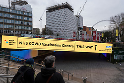 © Licensed to London News Pictures. 18/01/2021. LONDON, UK. Signage outside Wembley Park tube station directs the public to a vaccination centre at the Olympic Office Centre in Wembley, north London.  This is one of ten new mass Covid vaccination centres opening today and they join the seven already in use across the country.  So far, 3.8 million people across the UK have received a first dose and the government hopes that number to rise to 15 million by 15 February.  Photo credit: Stephen Chung/LNP